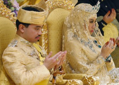 """Brunei's newly wed royal couple, Prince Abdul Malik and Dayangku Raabi'atul 'Adawiyyah Pengiran Haji Bolkiah, pray during the """"bersanding"""" or enthronement ceremony at their wedding in the Nurul Iman Palace in Bandar Seri Begawan April 12, 2015. Malik is the son of Brunei's Sultan Hassanal Bolkiah, one of the world's richest men. REUTERS/Olivia Harris TPX IMAGES OF THE DAY"""